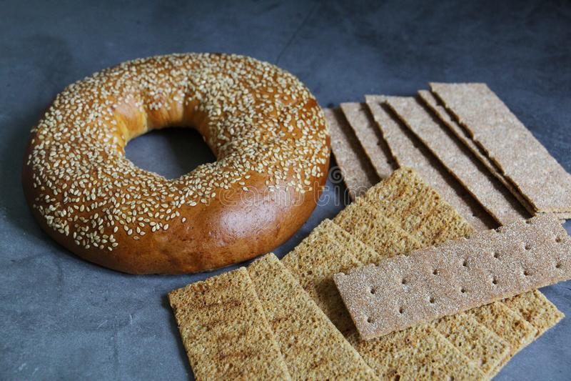 En ny bagel med sesamfr? N?rliggande ?r den tunna kn?ckebr?det arkivfoto