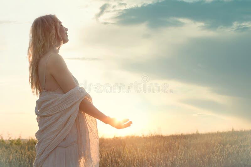 En ny dag börjar med soluppgången som skyddas i händerna av en kvinna arkivfoto