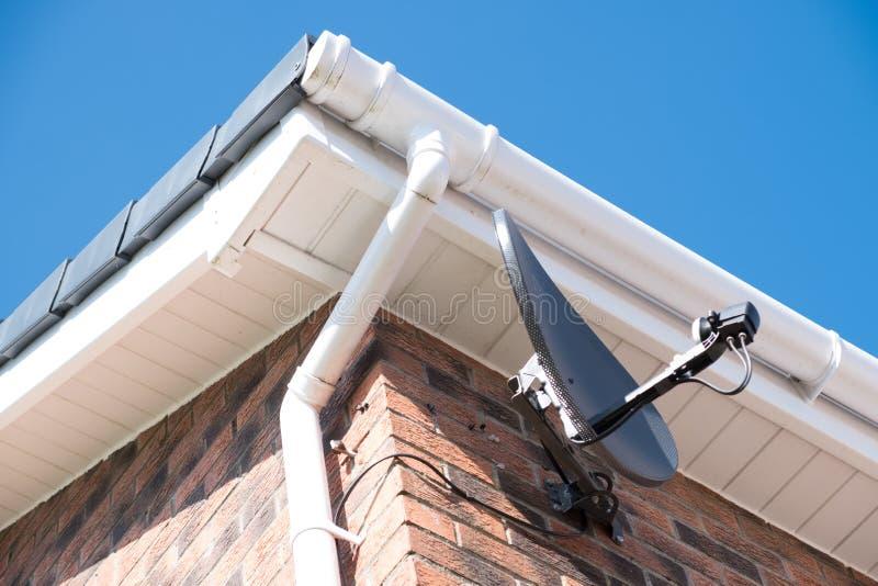 En ny installerad satellit- matr?tt p? sidan av en bostads- byggnad royaltyfri bild