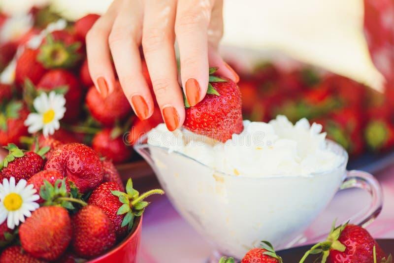 En ny jordgubbe med kräm i en bunke på en tabell i en sommarträdgård dekoreras med kamomillblommor som handen tar med en lo royaltyfri fotografi