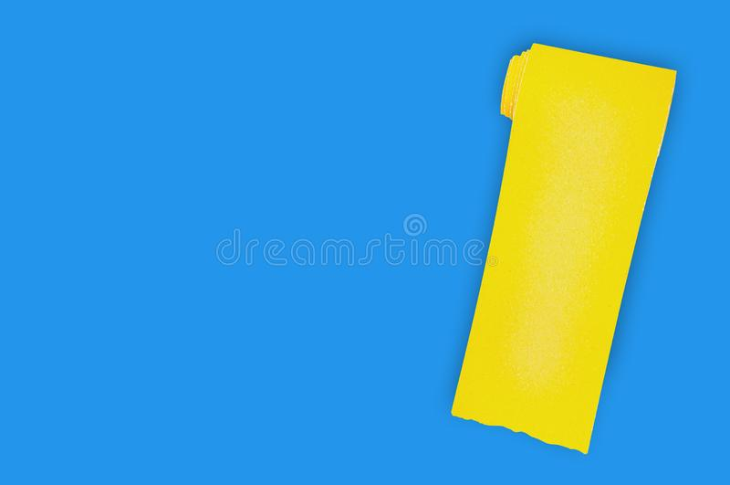 En ny rulle av gul slipande sandpapper f?r rastertr?- eller metallobjekt p? den bl?a tabellen i seminarium kopiera avst?nd f?r di royaltyfri foto