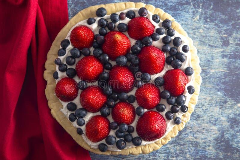 En ny sommarpaj för jordgubbe och för blåbär på en bekymrad blå trätabell royaltyfria bilder