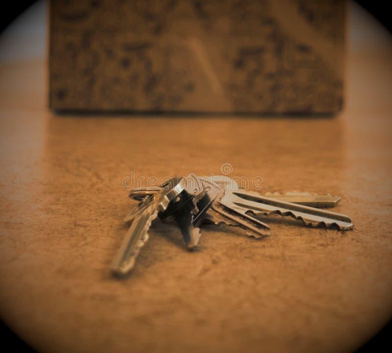 En nyckel- kedja med flera tangenter ligger på ett lägenhetgolv framme av en kartong arkivfoto