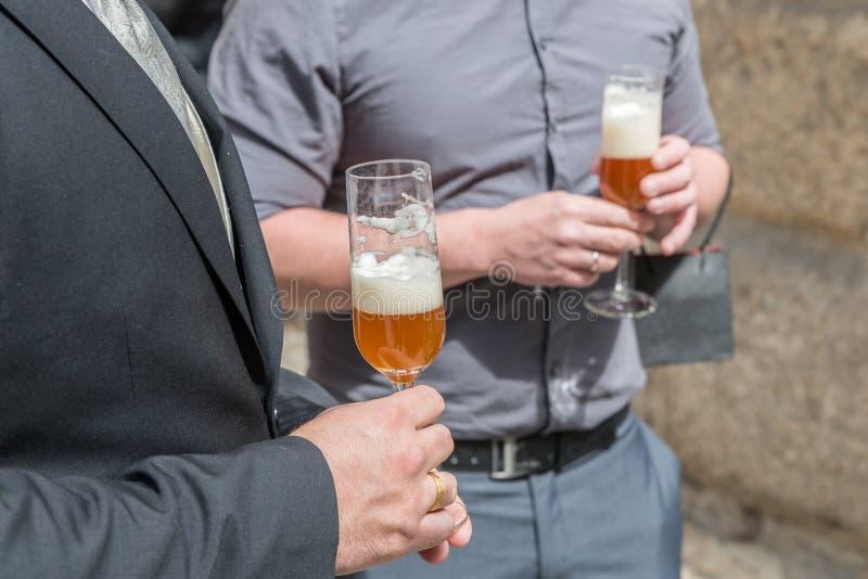 En nygift personmake och hans bästa man som dricker ett exponeringsglas av öl, Tyskland royaltyfri bild
