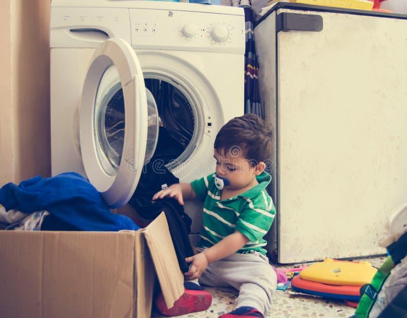 En och de gamla halva åren behandla som ett barn pojken som sätter kläder i tvagningmaskin arkivfoton