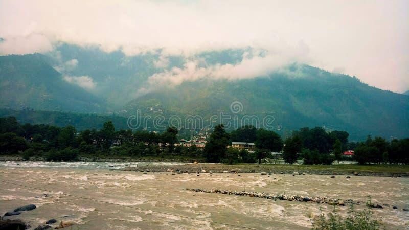 En oerhörd sikt av floden, molnet och berg i Manali, Indien arkivfoto