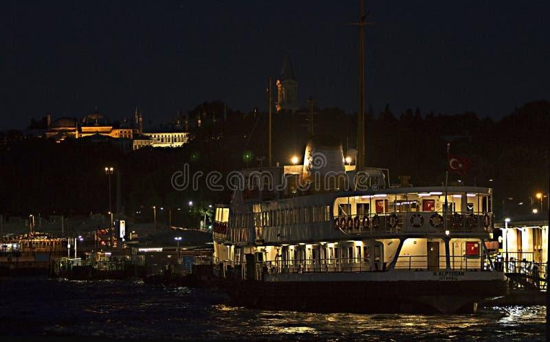 En offentlig färja som kallas 'Vapur 'på Eminonu port under den Topkapi slotten av ottomanvälden vid natt royaltyfria foton