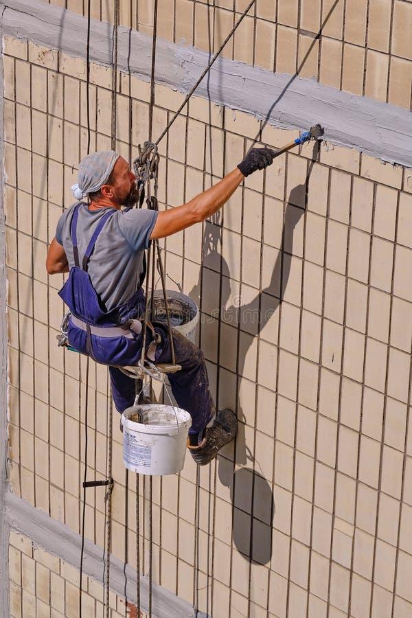 En offentlig servicearbetare bearbetar väggen av en byggnad för isolering, stänger mellanrummen och annullerar arkivfoton