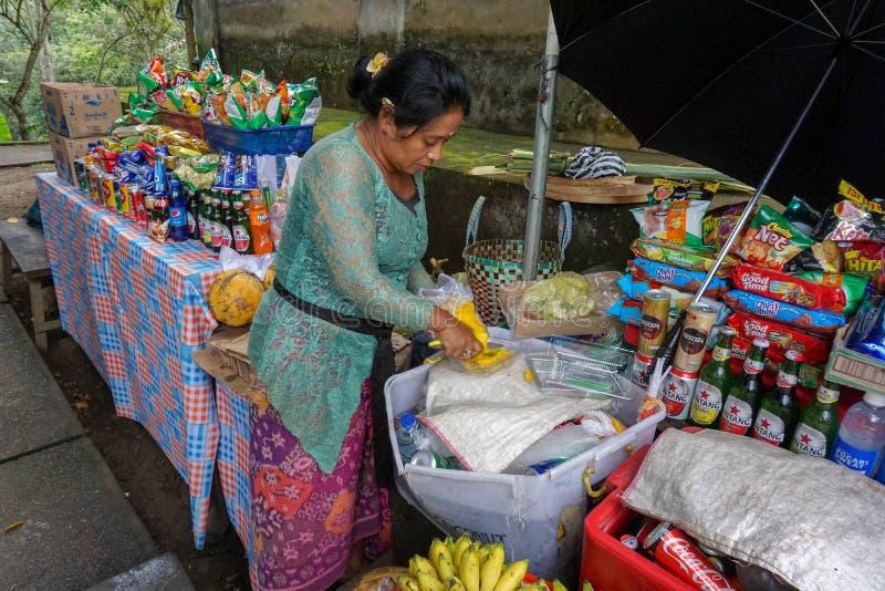En oidentifierad asiatisk försäljare som säljer tropisk exotisk ny frukt på gatan, Bali, Indonesien, 11 08 2018 royaltyfria foton