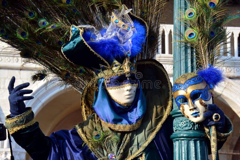 En oidentifierad man i blå maskeradkläder med påfågelfjädern på baksidan håller en maskering i vänstersidahanden under den Venedi arkivbilder
