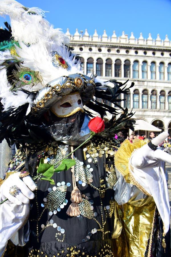 En oidentifierad man i svart maskeradkläder håller en röd ros i hand under den Venedig karnevalet arkivfoto