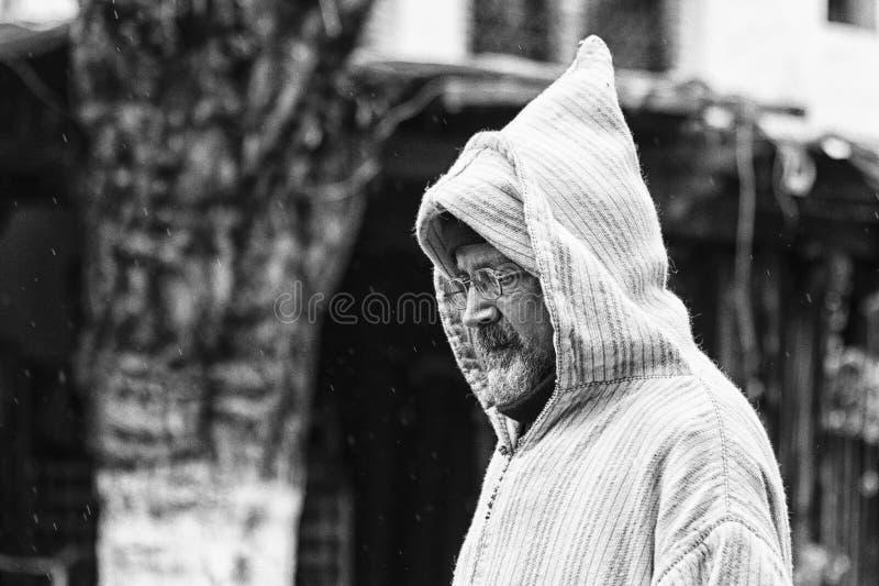 En oidentifierad man i typiska moroccan kläder, i en gata i den blåa Medinaen av Chefchaouen royaltyfri bild
