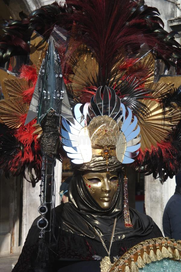 En oidentifierad man och klänningar utarbetade maskeradkläder med den guld- röd och svart fjäderhatten för maskeringar, under den arkivbilder