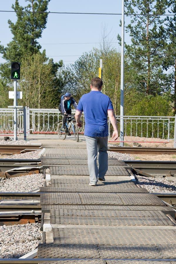 En oidentifierad man som korsar tyst järnvägen på en övergångsställe på en grön trafikljussignal arkivbilder