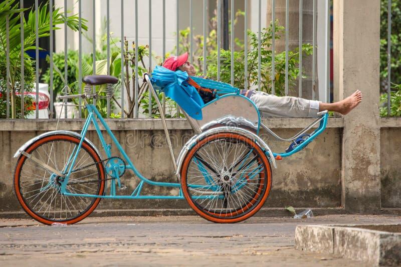 En oidentifierad rickshawchaufför väntar på klienter royaltyfria bilder