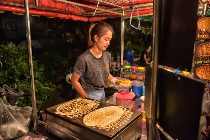 En oidentifierad thailändsk man som lagar mat Roti Mataba den till salu handelsresanden på gatanattmarknaden royaltyfria foton