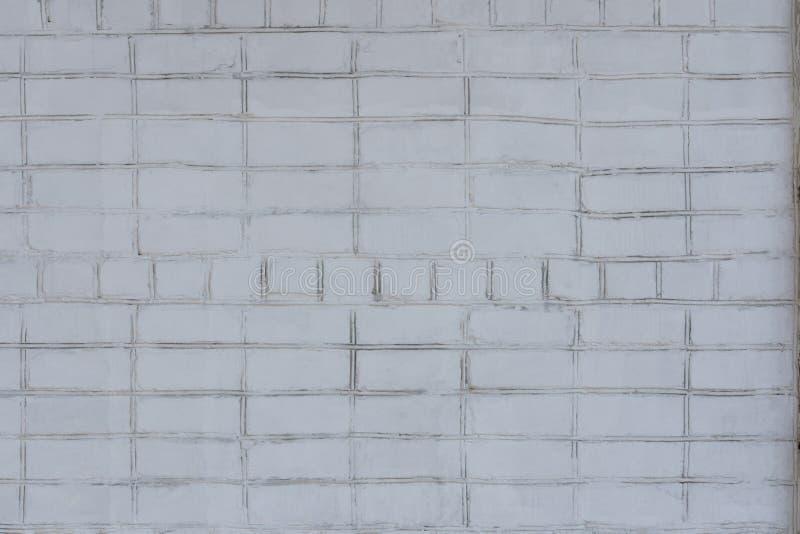 En ojämn vägg för gammal tegelsten målade ojämnt vitt Mest bra för bakgrunder arkivbild