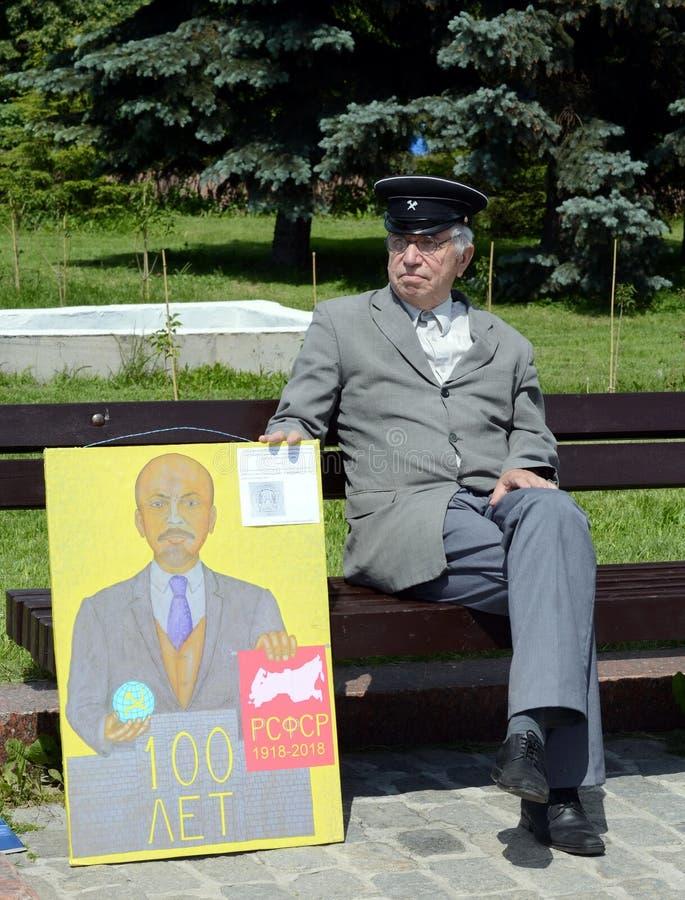 En okänd äldre man med en kommunistisk affisch på den Poklonnaya kullen av Moskva royaltyfria bilder
