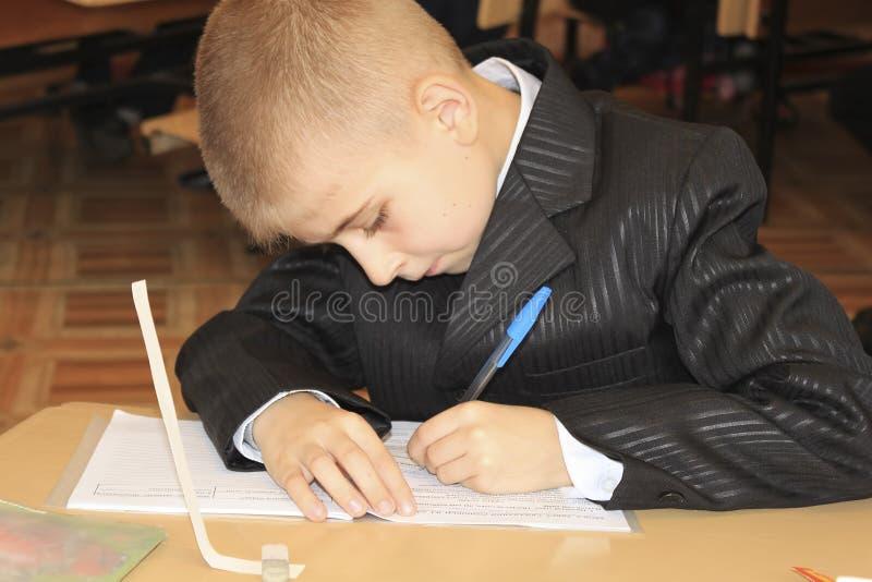 En okänd pojke sitter på tabellen i klassrumet och skriver något i en anteckningsbok royaltyfri foto