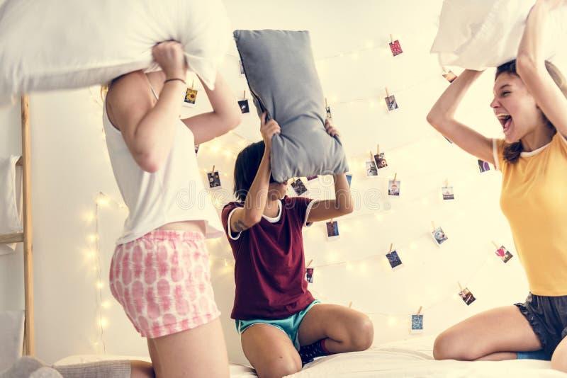 En olik grupp av kvinnor som spelar kuddekamp på säng tillsammans arkivbild