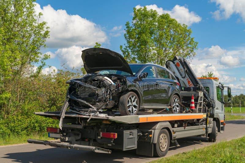 En olycksbil har laddats på en bärgningsbil arkivbild