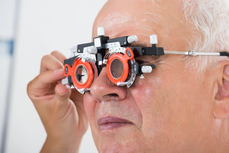 En optometriker Checking Patient Vision med försökramen arkivfoto