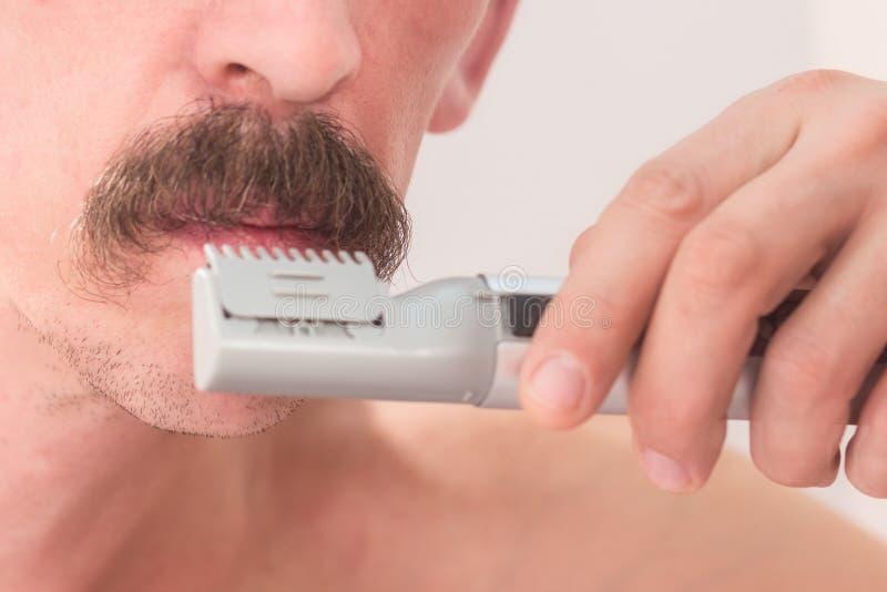 En orakad man klipper hans mustasch med en beskärare Närbild fotografering för bildbyråer