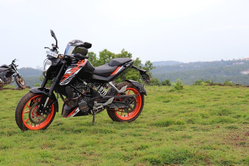 En orange sportmotorcykel som vilar på en grön kulle royaltyfri foto