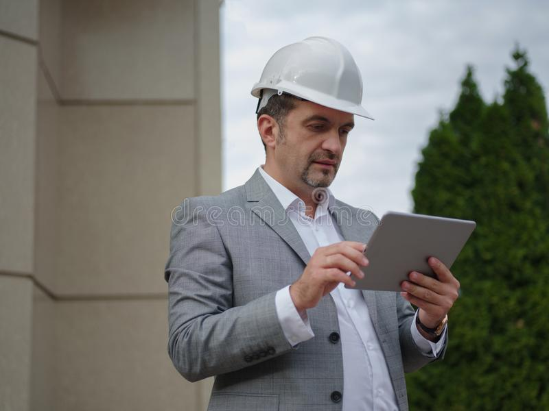 En ordförande med minnestavlan på en industriell bakgrund Byggmästare som använder elektronik Begrepp för byggnadsteknologier kop royaltyfria foton