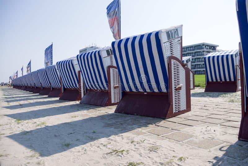 En ordning av taklade vide- strandstolar royaltyfria bilder