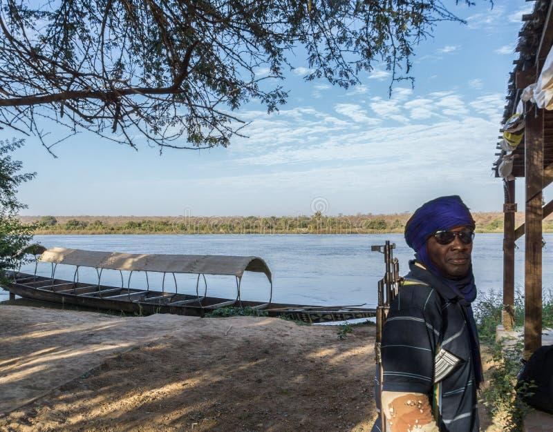 En ordningsvakt som patrullerar på Nigeret River, Niger, Västafrika arkivbilder