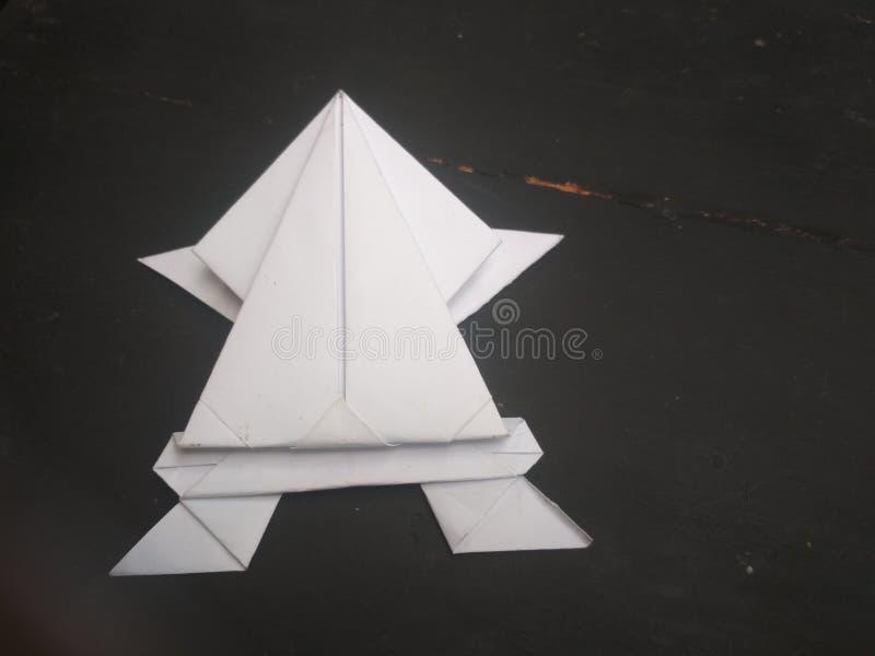 En origamigroda på en trätabell fotografering för bildbyråer