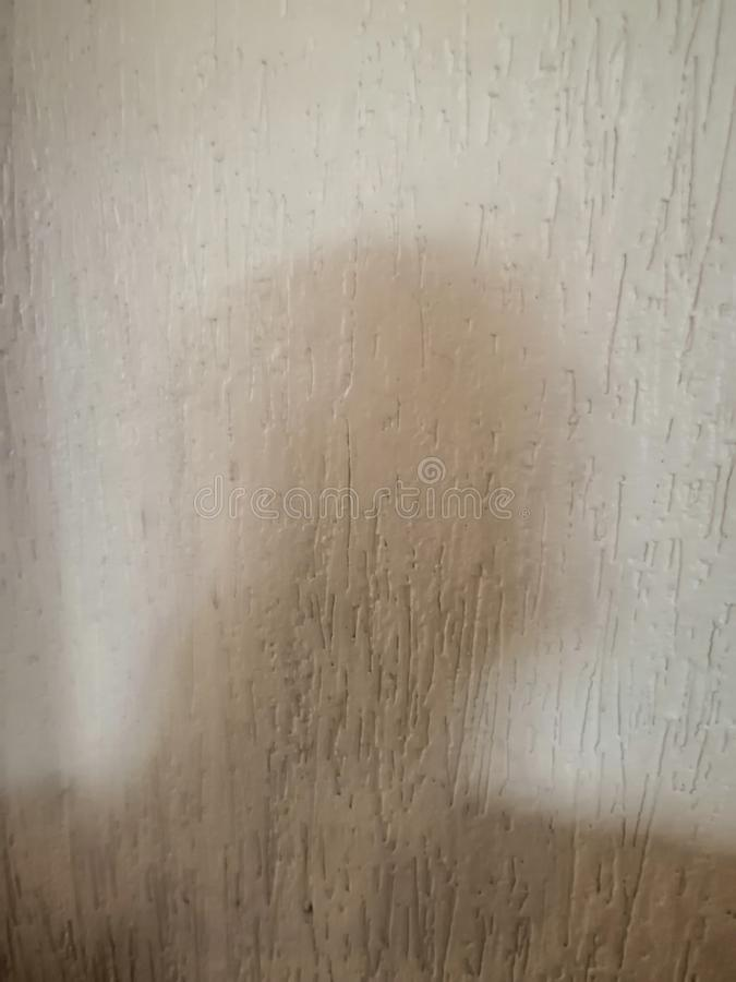 En oskarp skugga av en person på väggen arkivbild