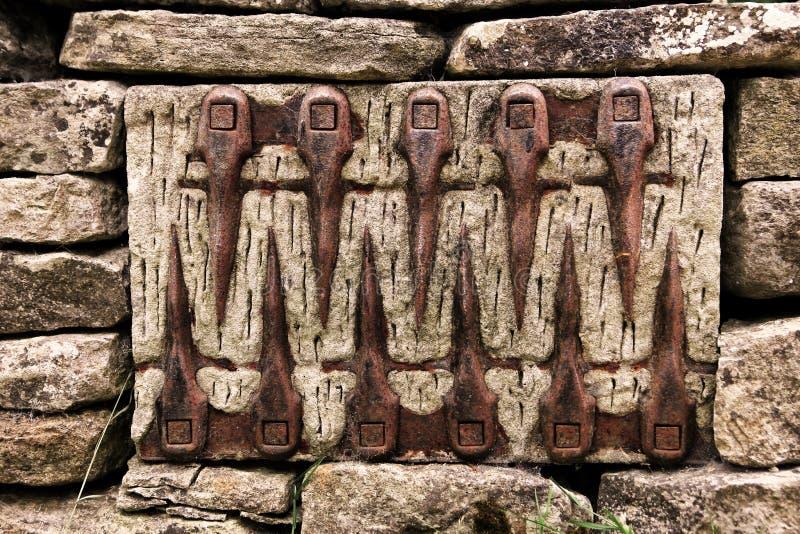 En ovanlig modell av den gamla lantgårdhjälpmedeluppsättningen in i en stenvägg royaltyfri bild