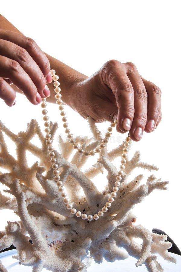 En pärlemorfärg halsband i hennes händer mot bakgrunden av korall royaltyfria bilder
