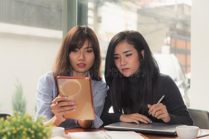 En-på-en möte Två unga affärskvinnor som sitter på tabellen i kafé Flickan visar information om kollega på bärbar datorskärmen arkivfoton