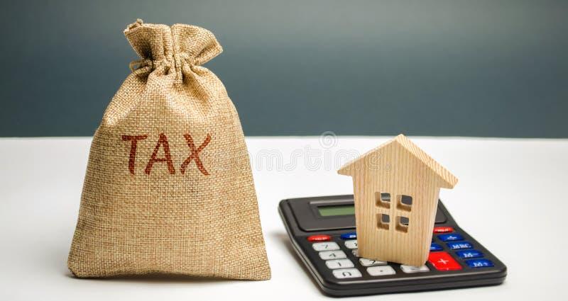 En påse med ordskatten och räknemaskin med ett hus Skatter på fastigheten, betalning Straff resterande skulder Register av skatte arkivbilder
