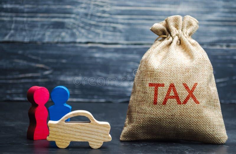 En påse med pengar och ordskatten och en bil med familjen Begrepp skattbetalningen för automatisk Medel väg, diskettskatt Är en e arkivfoto