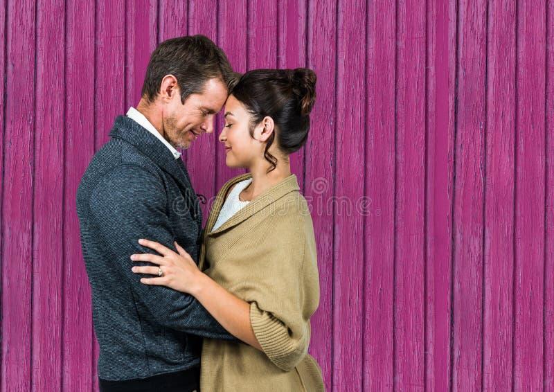 en paar die elkaar met roze houten achtergrond huging kijken royalty-vrije stock foto