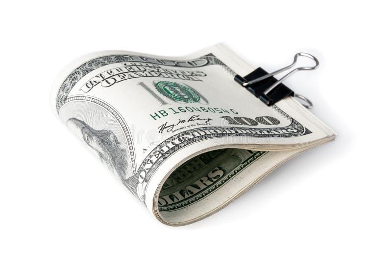 En packe av amerikanen hundra dollarräkningar vek i halvt och fäst med en prästerlig omfamning På en vit bakgrund royaltyfri foto