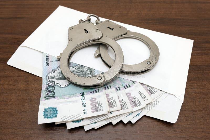 En packe av ryska rubel i ett kuvert och handbojor på en brun bakgrund Begreppet av kränkningen av lagen i financiaen arkivfoton