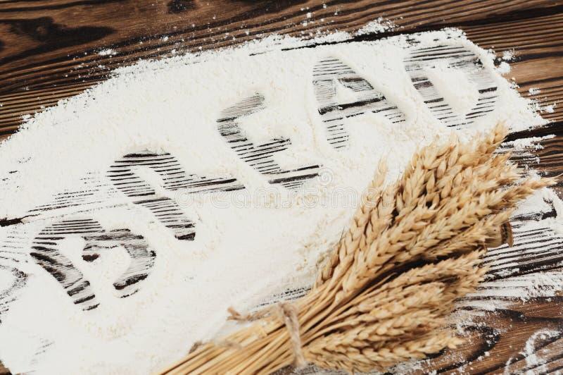 En packe av vete- och vallmo- och handskriftordet BRÖD på mjöl på gamla träplankor fotografering för bildbyråer