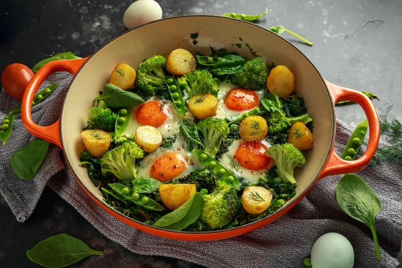 En Pan Green shakshuka med grönkål, broccoli, söta ärtor, spenat och dill med fria områdeägg, perfekt kvällsmål royaltyfri bild