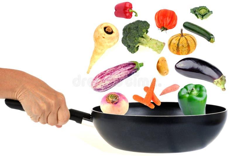 En panna stekte blandade grönsaker på en vit bakgrund royaltyfria bilder