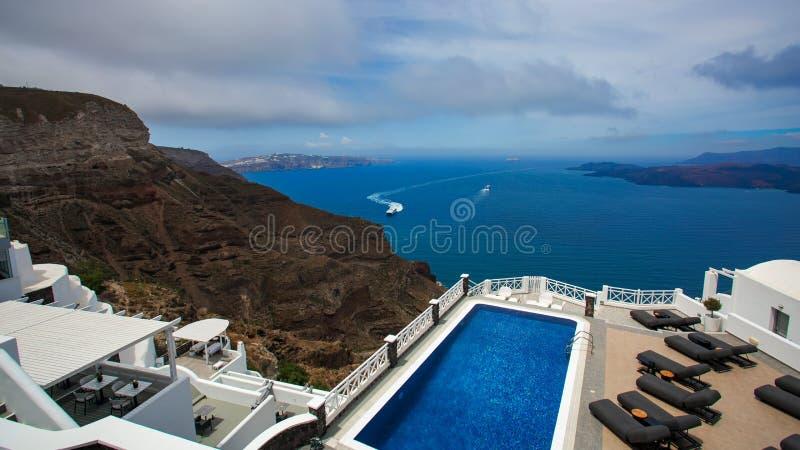 En panorama- bild från Santorini med semesterortsimbassängen och havssikt till calderaen arkivbild
