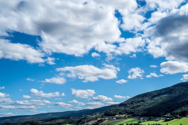 En panorama- och dramatisk cloudscape med många moln på en blå himmel över lantliga bergkullar, med idylliskt jordbruks- fotografering för bildbyråer
