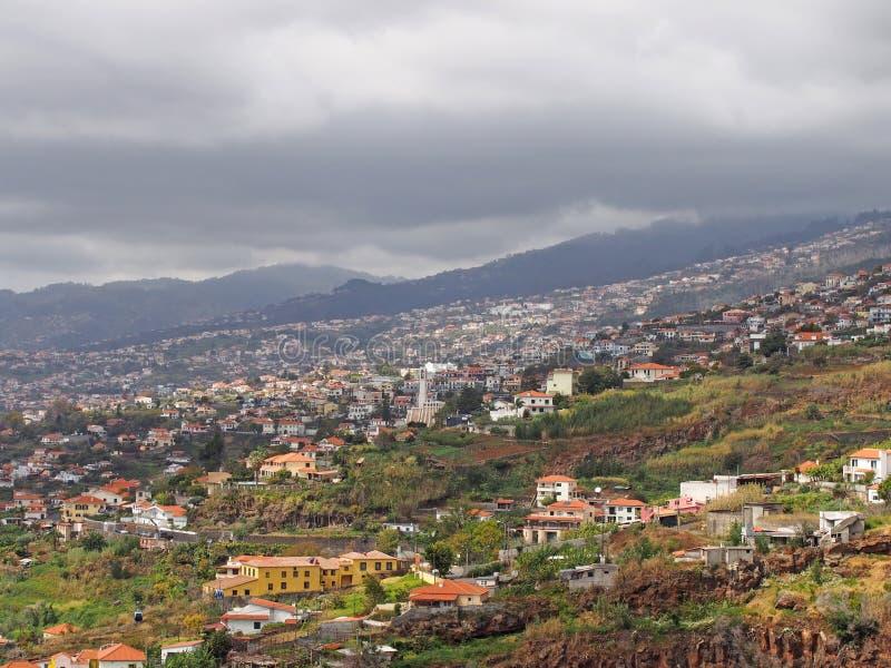 en panoramautsikt av funchal i madeira som visar små lantgårdar och jordbruk med byggnader av staden mot avlägset molnigt royaltyfria foton