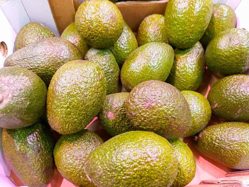 en paperboardask på marknadsöverflödet av smakliga briljanta gröna avokadon skördade precis klart att säljas till kunder royaltyfria bilder