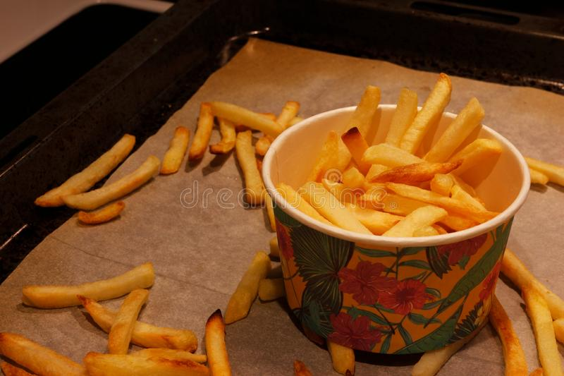 En pappers- kopp med pommes frites som står på en stekhet panna med spridd pommes frites arkivbild