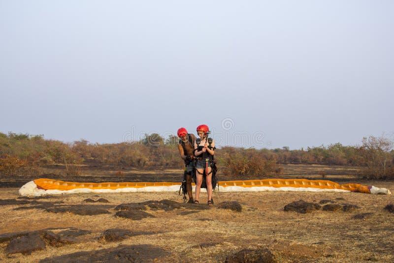 En paraglider som en man med ett grått skägg förbereder sig att ta av i tandemcykel med en flicka, mot a royaltyfri foto